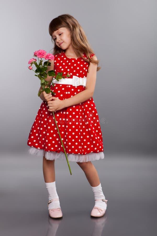 拿着花的微笑的小女孩 免版税图库摄影