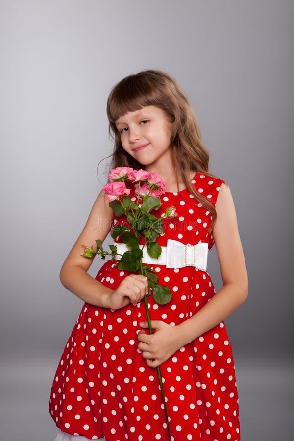 拿着花的微笑的小女孩 库存图片