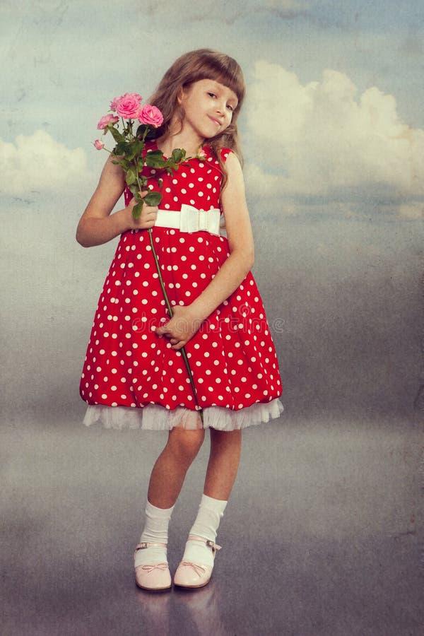 拿着花的微笑的小女孩 库存照片