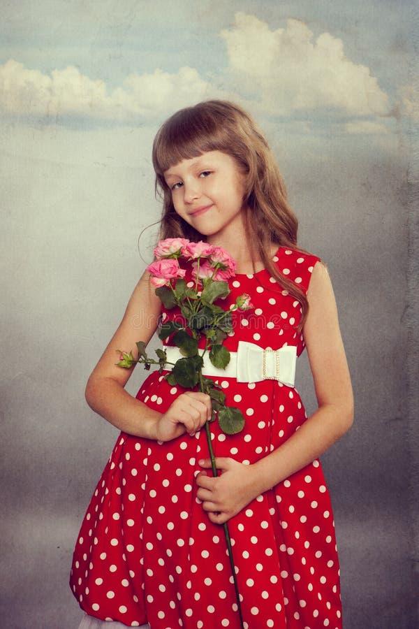 拿着花的微笑的小女孩 免版税库存照片