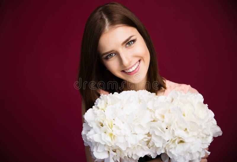 拿着花的微笑的美丽的妇女 库存照片