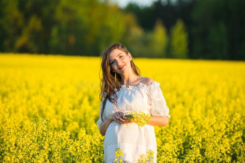 拿着花的怀孕的女孩 孕妇的腹部 怀孕的概念 在绿色自然被弄脏的背景 ?? 库存图片