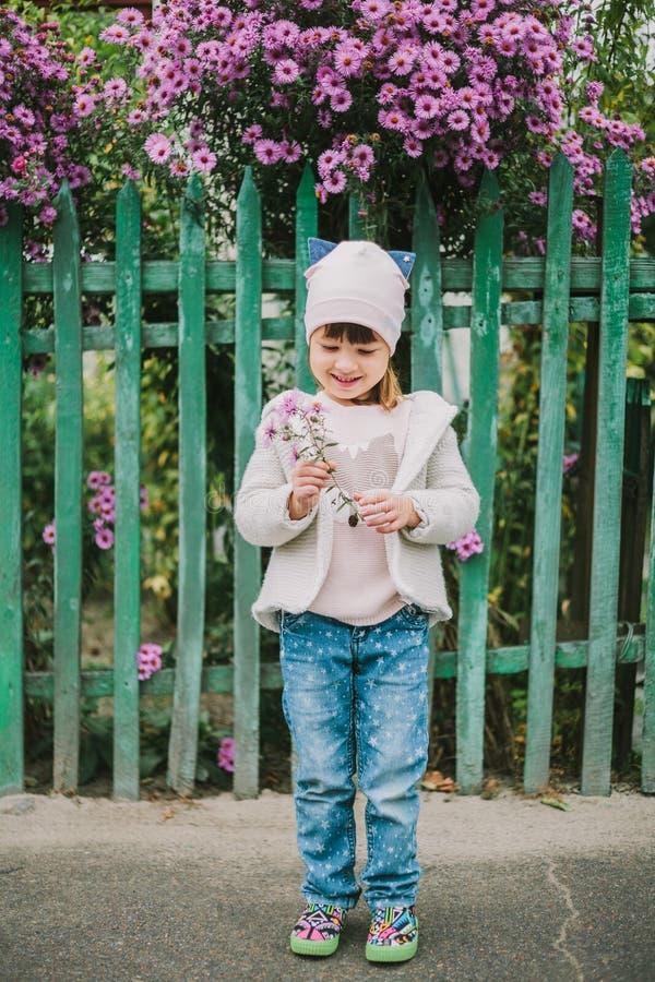 拿着花的愉快的女孩 在绿色篱芭背景  库存照片