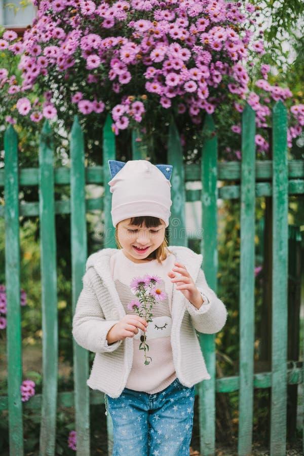 拿着花的愉快的女孩 在绿色篱芭背景  免版税图库摄影