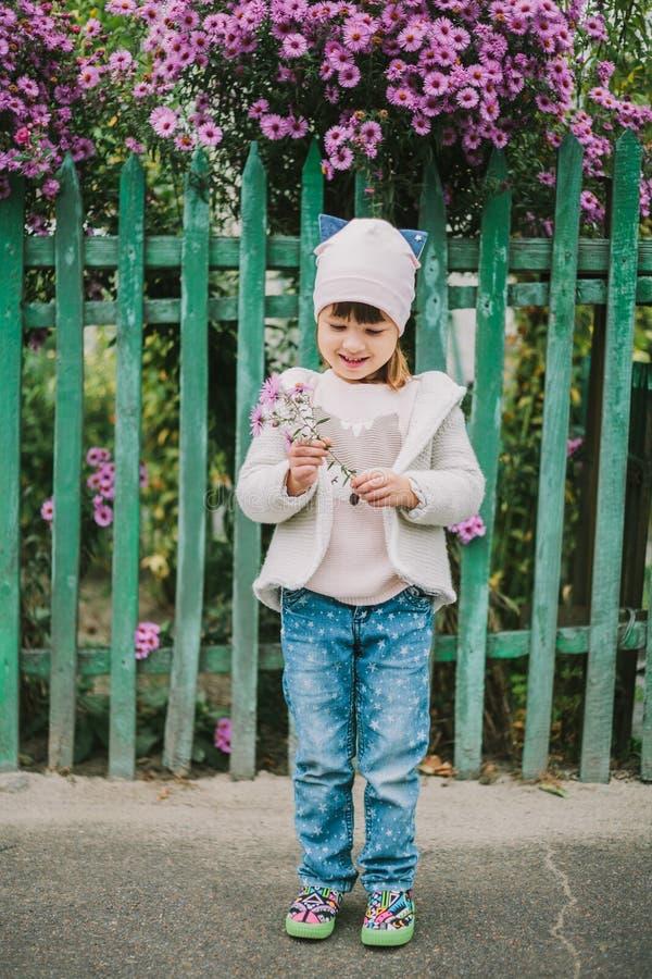 拿着花的愉快的女孩 在绿色篱芭背景  免版税库存图片