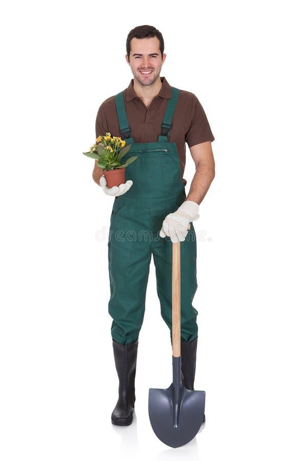 拿着花的愉快的新花匠 免版税库存照片