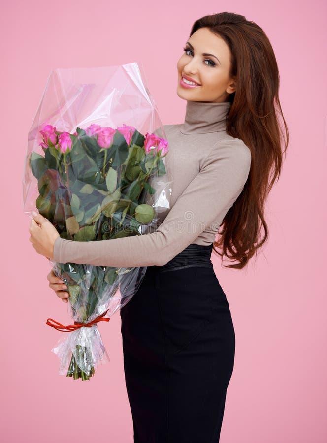 拿着花的愉快的棕色毛发的少妇 免版税库存照片