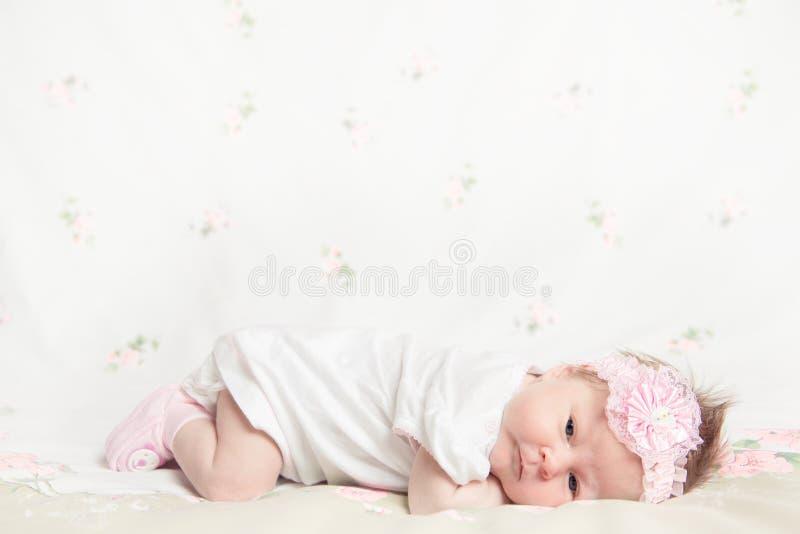 拿着花的美丽的新出生的女孩 免版税库存照片