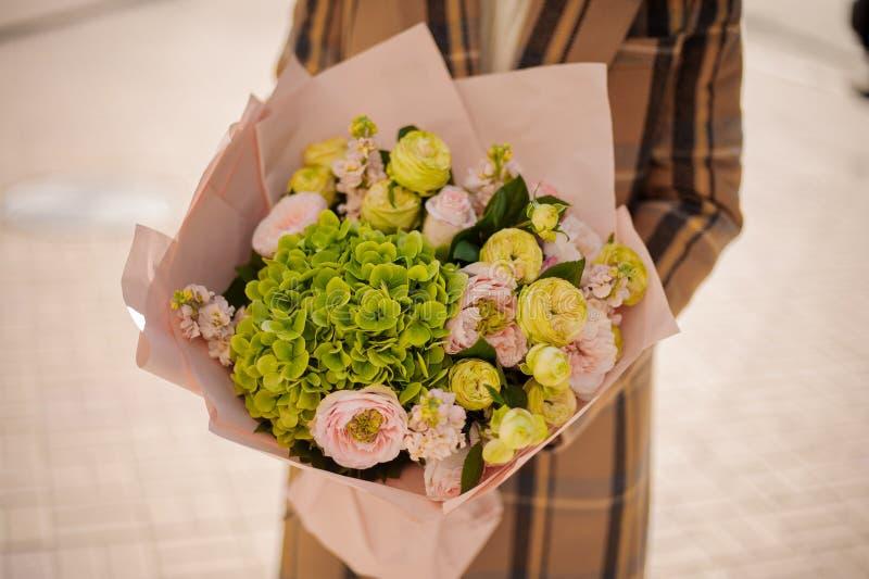 拿着花的美丽的花束妇女包裹在工艺pa 免版税库存图片