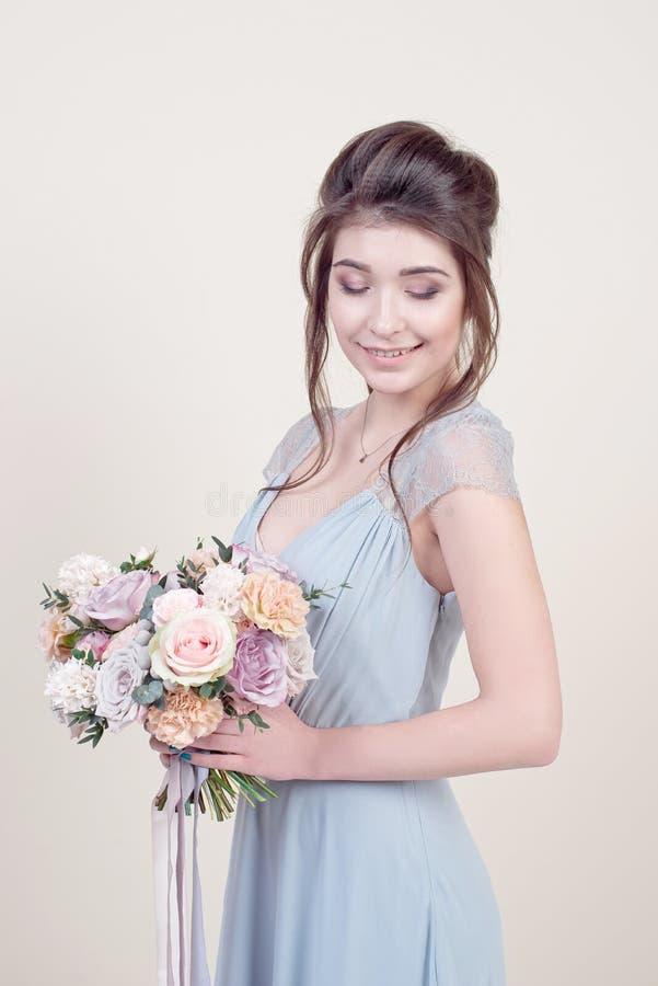 拿着花的花束半身美好的女性模型佩带在背景隔绝的豪华长的有花边的礼服 免版税库存照片