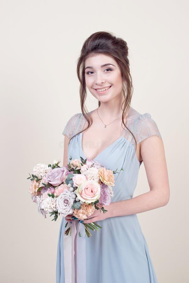 拿着花的花束半身美好的女性模型佩带在背景隔绝的豪华长的有花边的礼服 免版税库存图片