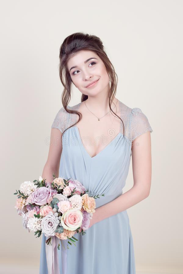 拿着花的花束半身美好的女性模型佩带在背景隔绝的豪华长的有花边的礼服 库存图片