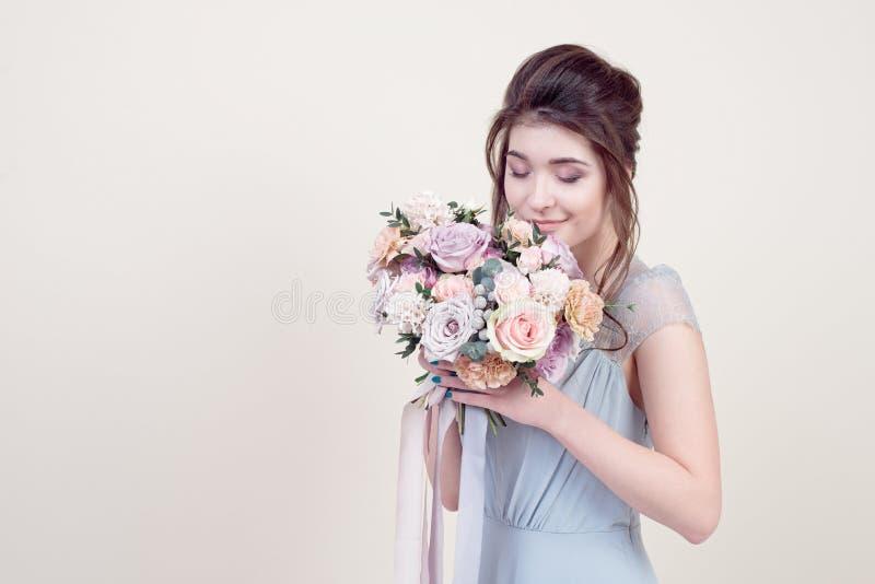 拿着花的花束半身美好的女性模型佩带在背景隔绝的豪华长的有花边的礼服 库存照片