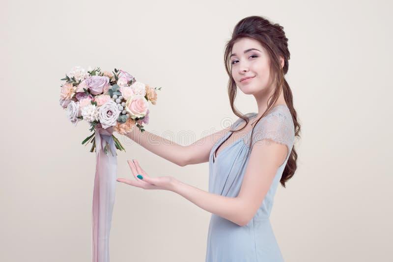 拿着花的花束半身美好的女性模型佩带在背景隔绝的豪华长的有花边的礼服 免版税图库摄影