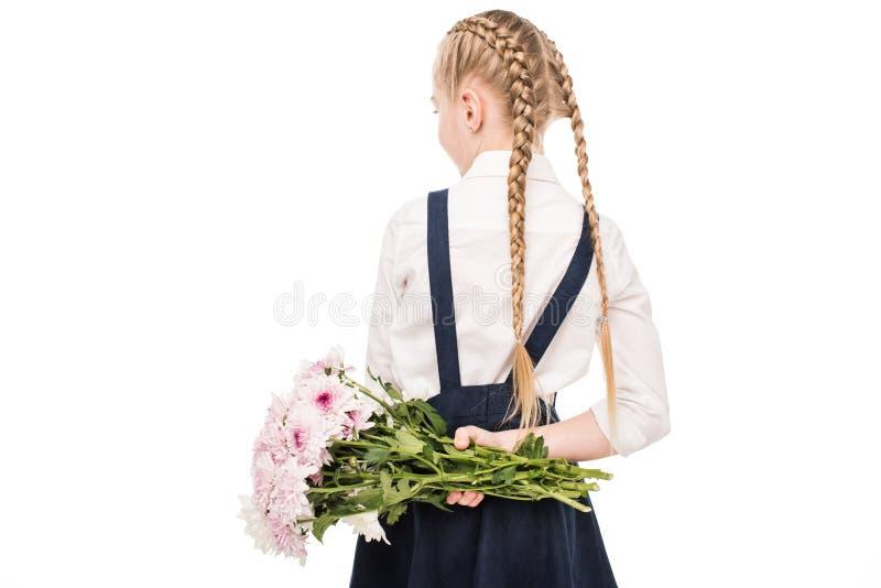 拿着花的花束后面观点的逗人喜爱的小女孩 库存照片