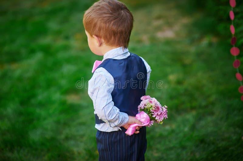 拿着花的花束在他的后的小男孩  图库摄影