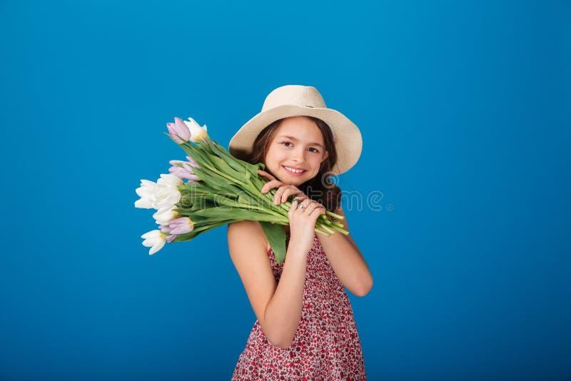 拿着花的花束帽子的微笑的可爱的小女孩 免版税图库摄影