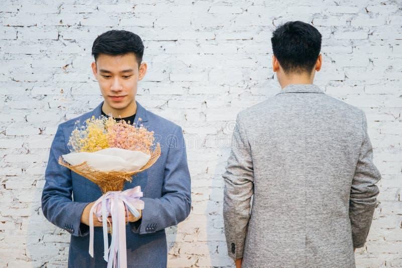 拿着花的花束快乐夫妇,准备给他的特殊场合或婚姻的提案的伙伴 免版税图库摄影