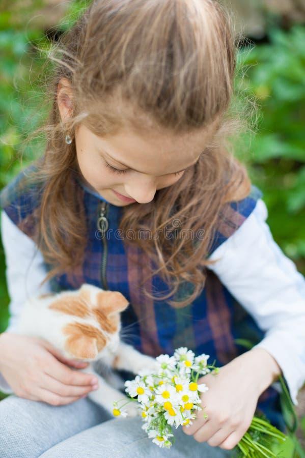 拿着花的花束愉快的小女孩使用与在她的手上的小的猫 库存照片