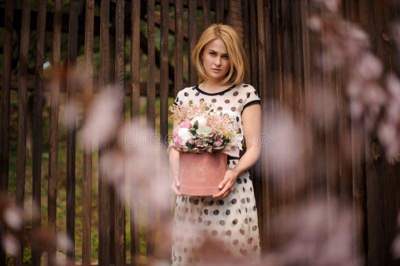 拿着花箱子的白肤金发的妇女站立在背景  免版税库存照片
