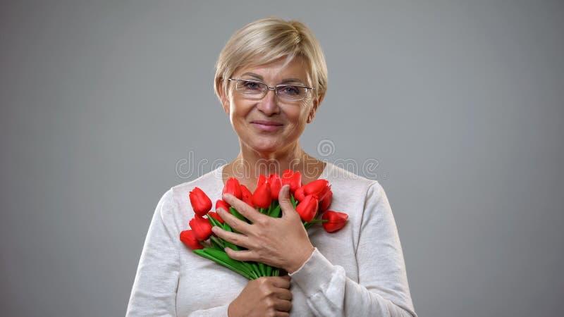 拿着花花束和看照相机的老妇人,从钦佩者出席 免版税库存照片