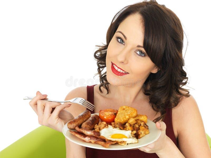 拿着英式早餐的板材年轻愉快的妇女 免版税图库摄影