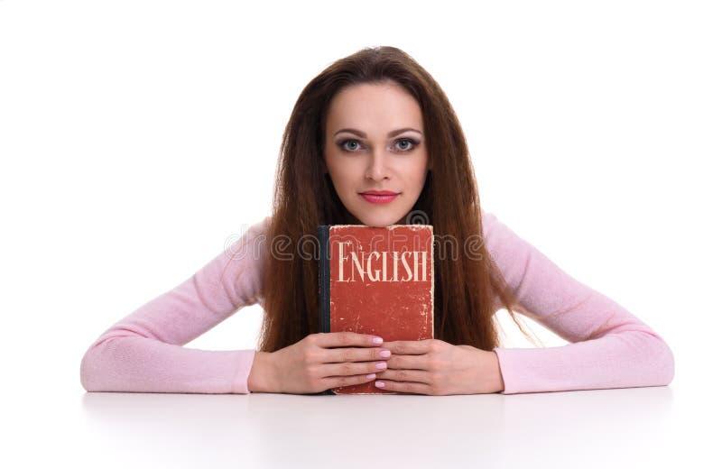 拿着英语字典的俏丽的妇女 免版税库存图片
