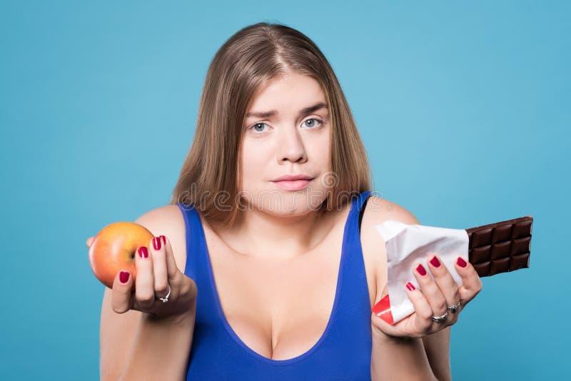 拿着苹果和巧克力的半信半疑的胖的夫人 免版税库存图片