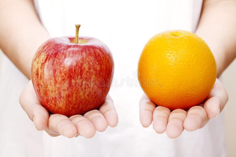拿着苹果和桔子的手 库存照片