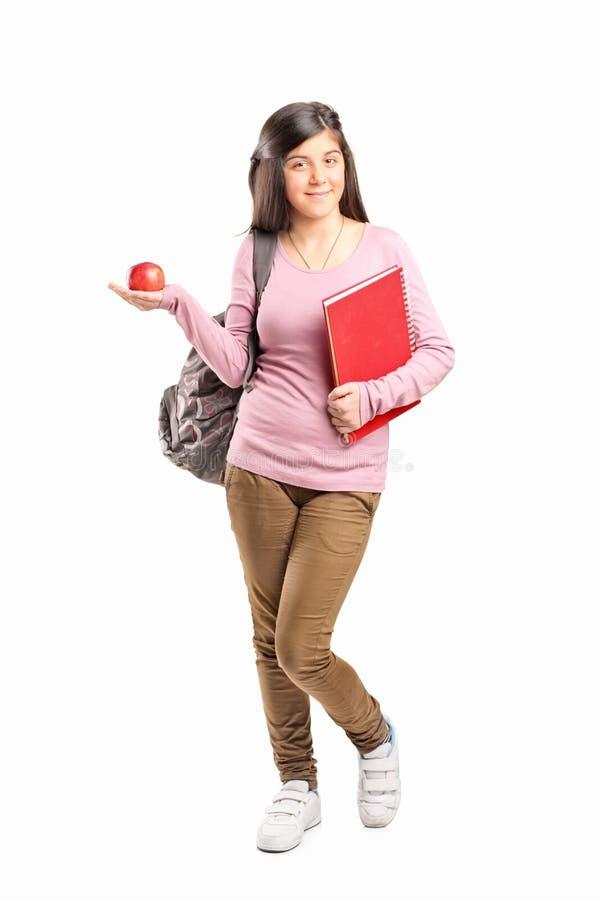 拿着苹果的女小学生 库存图片