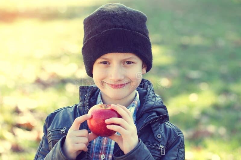 拿着苹果的小行家男小学生 免版税库存图片