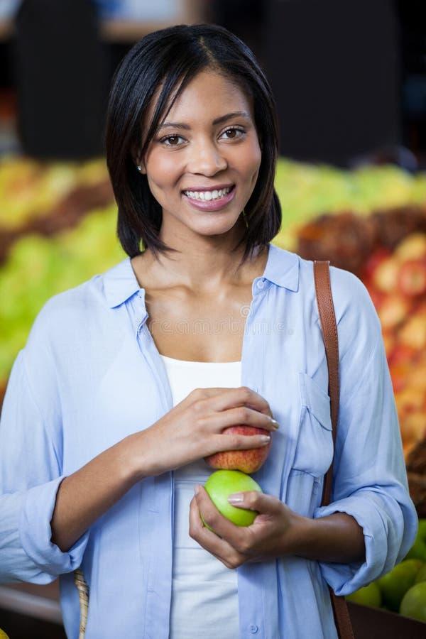 拿着苹果的美丽的妇女画象 图库摄影