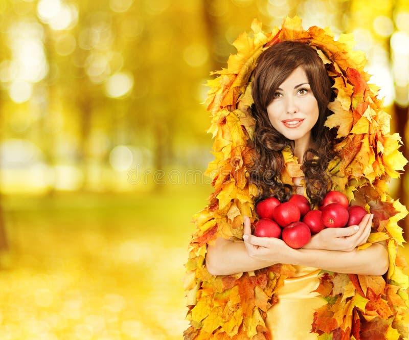 拿着苹果,在黄色秋天的时装模特儿的秋天妇女离开 库存图片