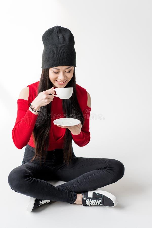 拿着茶杯的可爱的亚裔妇女被隔绝 免版税库存照片