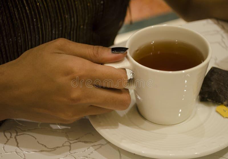 拿着茶杯的女孩的图象 免版税库存照片