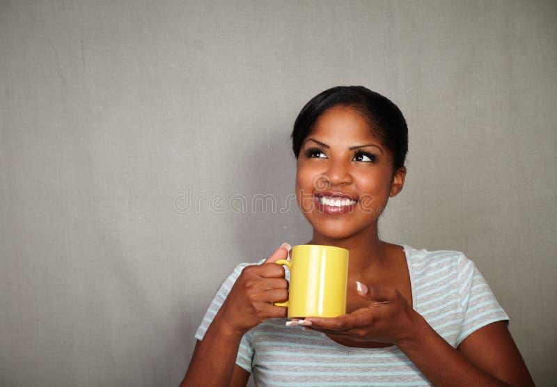 拿着茶杯的年轻非洲妇女 库存图片