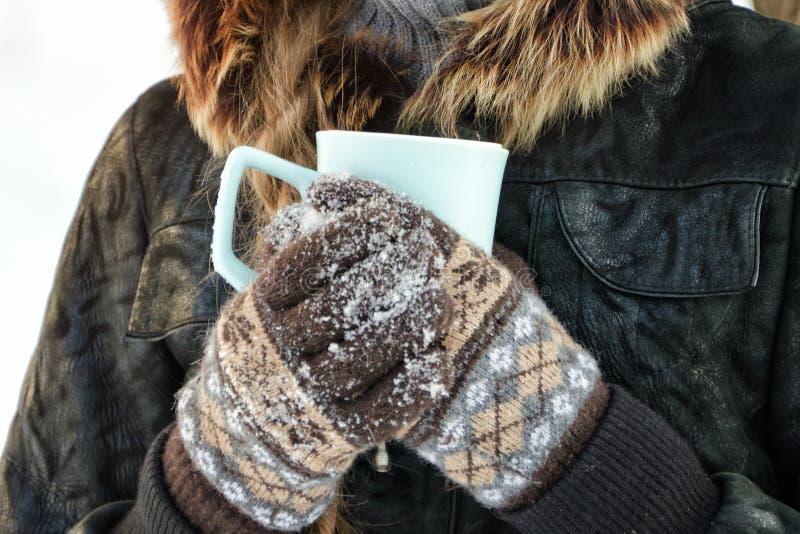 拿着茶的手套的女孩 冬天 关闭 免版税库存图片
