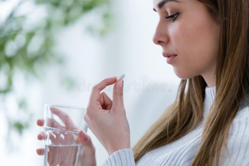 拿着药片和杯水的沮丧的少妇,当在家时看此 库存图片
