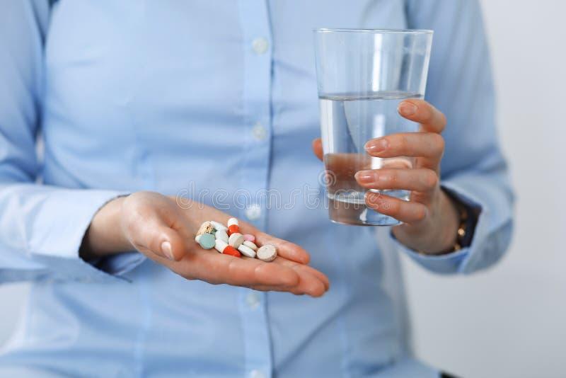 拿着药片和杯水,手特写镜头的年轻未知的妇女  医学和医疗保健概念 图库摄影