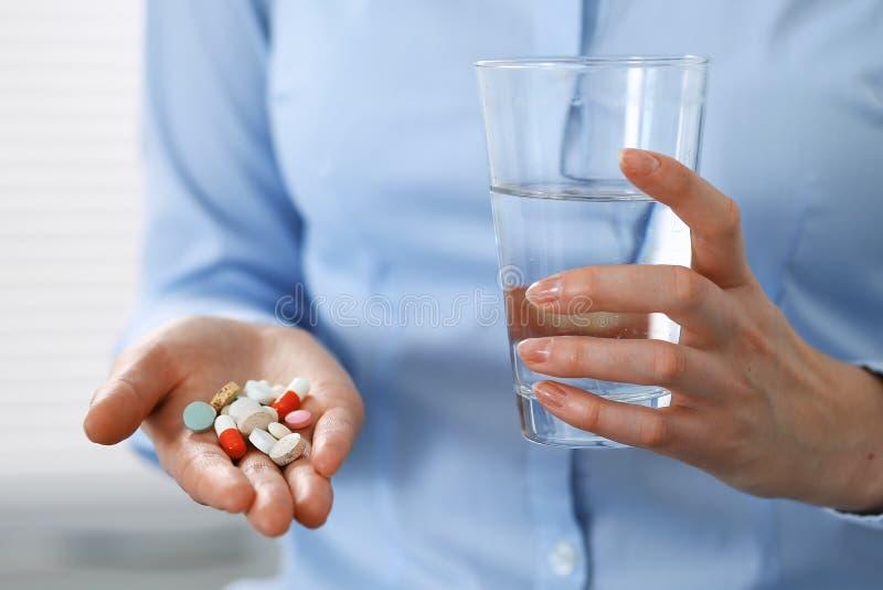 拿着药片和杯水,手特写镜头的年轻未知的妇女  医学和医疗保健概念 库存图片