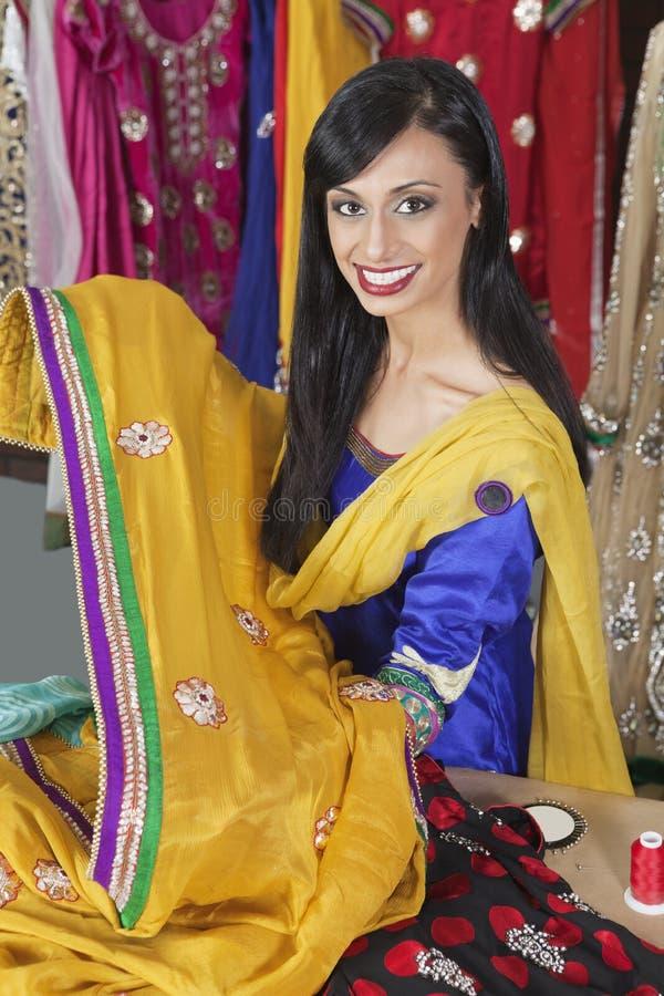 拿着莎丽服的印地安女性裁缝的画象 免版税库存照片