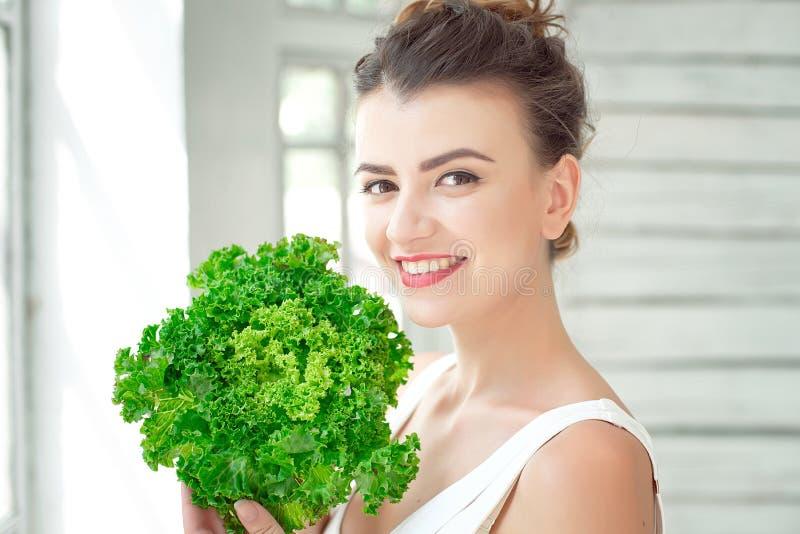 拿着莴苣的绿色叶子年轻逗人喜爱的女孩 Healtlife概念 室内射击 图库摄影