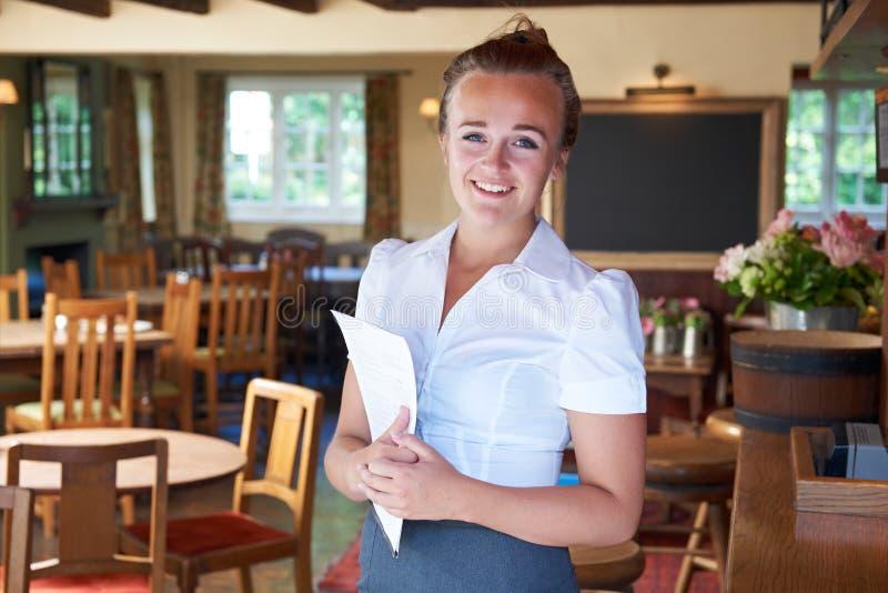 拿着菜单的女服务员画象在餐馆 图库摄影
