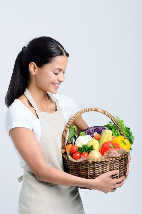 拿着菜的篮子可爱的妇女 免版税库存图片