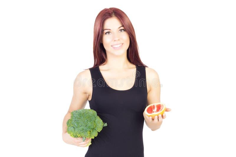 拿着葡萄柚和硬花甘蓝的微笑的秀丽妇女 妇女坐饮食 素食主义者食物 图库摄影