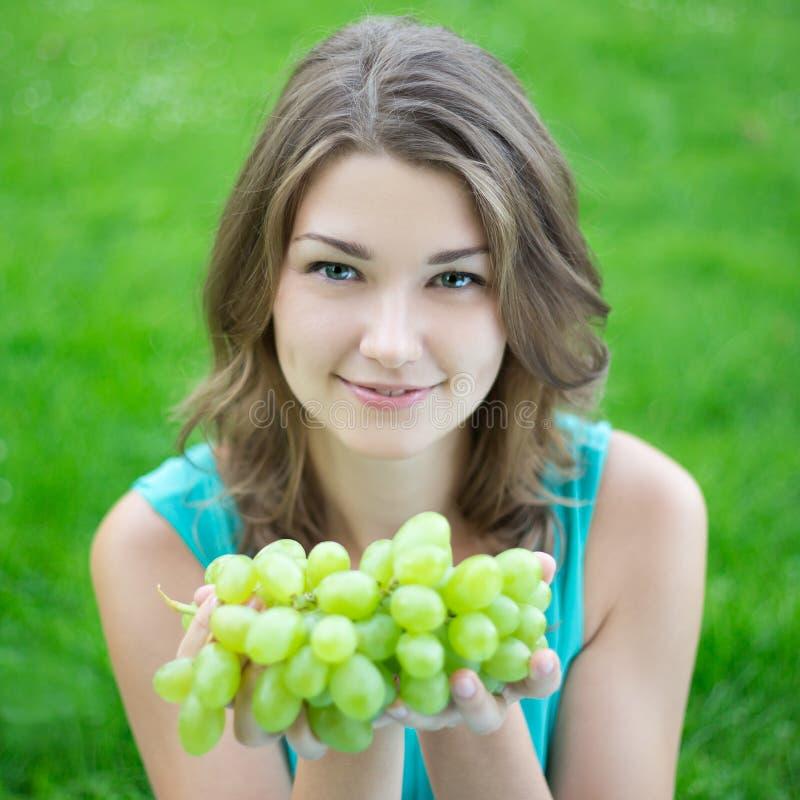 拿着葡萄的美丽的妇女 库存照片