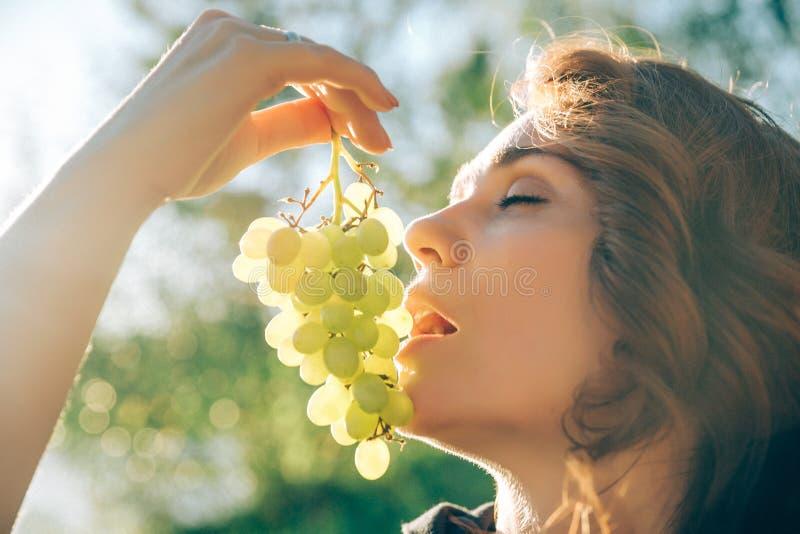 拿着葡萄的年轻美丽的妇女画象,要吃草莓,在绿色背景夏天自然,日落 免版税库存照片