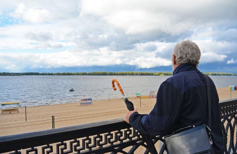 拿着葡萄酒伞的老人看 图库摄影