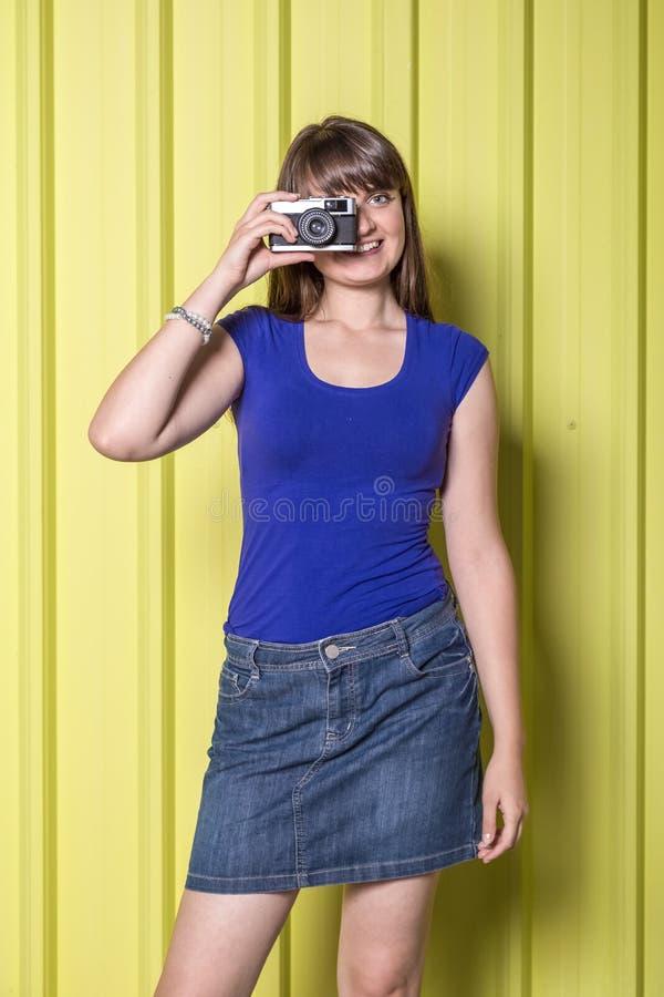 拿着葡萄酒影片照相机的时兴的女孩对金墙壁 免版税库存图片