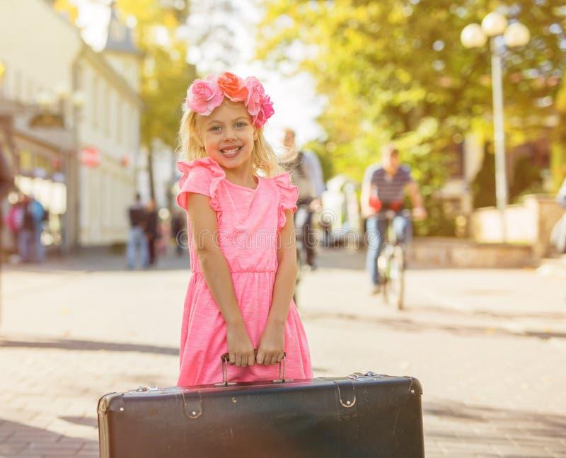 拿着葡萄酒手提箱的小女孩 库存图片